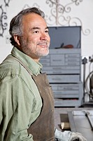 Happy mature man looking away while standing in workshop