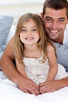 Portrait of smiling father and daughter lying together in bed