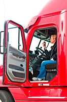Pretty blonde woman in a big rig talking on her CB radio to other truck drivers.