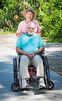 Senior lady pushing her husband in his wheelchair.