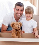 Smiling father and daughter with a teddy bear moving home