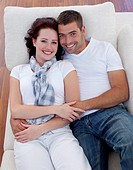 High angle of young couple lying together on sofa
