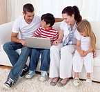 Happy family at home using a laptop