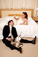 Bride and groom toasting in hotel room (thumbnail)