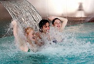 Young people standing under water spray in spa pool (thumbnail)