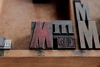 the letter M in different sizes and fonts in a wood type case, focus on the intricate, decorative metal one bbbb