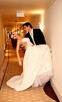 Groom carrying bride into hotel room (thumbnail)