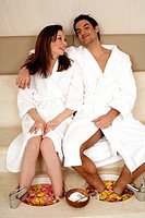A young couple enjoying a foot bath with rose petals