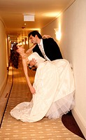 Groom carrying bride into hotel room