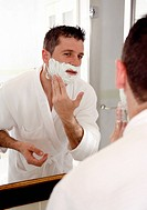 Man shaving in front of mirror