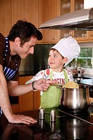 Father and son cooking spaghetti