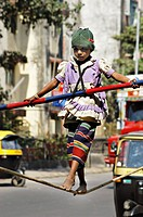 South Asian Girl Working Street Performer Balancing Act By Walking On Rope With Bamboo In Hand