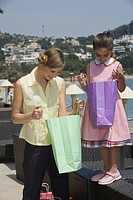 Mother and daughter looking in shopping bags
