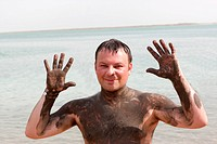 A man with Mineral mud body on a beach of Dead sea