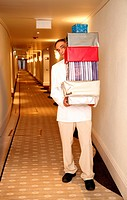 Bellboy carrying gift boxes down hallway