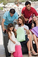 Two couples and child with shopping bags