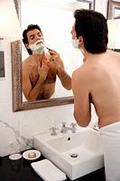 Man shaving in the bathroom mirror