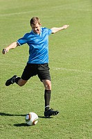 Soccer player kicking soccer ball on soccer field