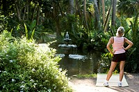 Woman in her 50s exercising in park, enjoying nature and view of fountain in pond