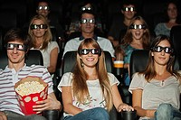 Audience wearing 3_D glasses in movie theater