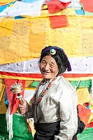 Tibetan Buddhism, devout Tibetan with prayer wheel in front of colorful prayer flags, Barkhor Square, Lhasa, Himalayas, Tibet, China, Asia