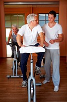 Fitness trainer giving spinning classes to senior people