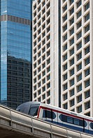 A mass transit train on an elevated track passes modern buildings in the central business district of Bangkok. Public transport