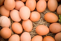Fresh eggs arranged in a straw barn setting.