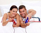 Happy young couple having fun playing videogames in bed
