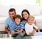 Portrait of happy family smiling at the camera in living_room