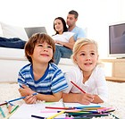 Children painting in living_room and parents using a laptop on sofa