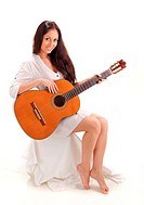 Young beautiful smiling brunette lady in white chemise playing acoustic guitar