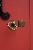 Closeup of red door with brass handle and lock