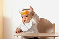 portrait of baby in high chair holding bowl with fruit