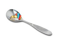 Spoon filled with daily pills to be taken at breakfast time, includes clipping path