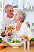Senior couple in love eating a salad in the kitchen and drinkng wine