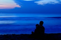 A father and son enjoying sunset at a tropical beach
