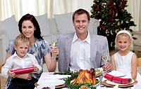 Parents toasting with champagne in Christmas dinner at home