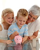 Close_up of grandmother and children saving money in a piggybank