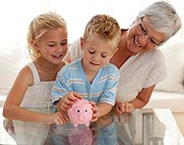 Smiling grandmother and children saving money in a piggybank