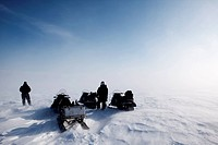 A blowing snow landscape with three snowmobiles on an expedition