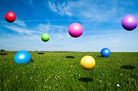 Colored balls jumping on a green meadow