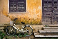 Bicycle leaning against the wall of an old house with yellow walls and purple shutters