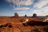 USA, Arizona, Monument Valley Navajo Tribal Park, Time exposure of truck headlights on road beneath red sandstone rock cliffs in Monument Valley under...