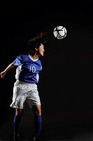 Japanese Young Sportswoman Hitting Soccer