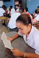 Secondary school girl reading book at desk,
