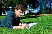 Young college student doing his homework in the park on a sunny day