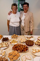 Voluntary workers with a display of cakes at an Age Concern show,