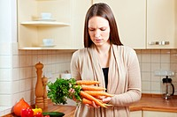 Seceptical woman checking on bunch of carrots in the kitchen