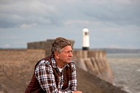 Mature Male looking out to sea with lighthouse in background